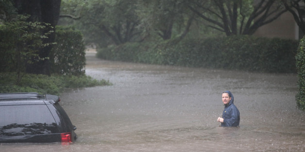 HOUSTON, TX - AUGUST 27:  A resident walks down a flooded street in the upscale River Oaks neighborhood after it was inundated with water from Hurricane Harvey on August 27, 2017 in Houston, Texas. Harvey, which made landfall north of Corpus Christi late Friday evening, is expected to dump upwards to 40 inches of rain in Texas over the next couple of days.  (Photo by Scott Olson/Getty Images)