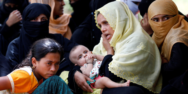 A Rohingya refugee woman with a child talks over phone as she takes shelter in No Man's Land between Bangladesh-Myanmar border, in Cox's Bazar, Bangladesh, August 27, 2017. REUTERS/Mohammad Ponir Hossain
