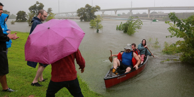 Area residents use a kayak to rescue motorists stranded on Interstate highway 45 which is submerged from the effects of Hurricane Harvey seen during widespread flooding in Houston, Texas, U.S. August 27, 2017. REUTERS/Richard Carson