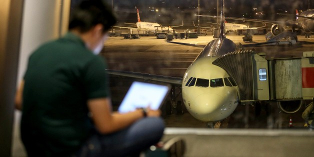 ISTANBUL, TURKEY - MARCH 22: A man checks his tablet computer at the departures lounge as an airliner is seen parked at the apron in the background at Ataturk International Airport in Istanbul, Turkey on March 22, 2017. United Kingdom's flag carrier airline British Airways has started to implement a ban which had issued by British government on all direct flights from the airports in Turkey, Lebanon, Egypt, Saudi Arabia, Jordan and Tunisia. The British government's ban applies to any electronica