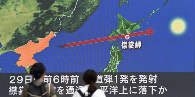 Des passants regardent le 29 août 2017 à Tokyo un écran montrant la carte du Japon et de la péninsule coréenne, d'où est parti le missile qui a survolé l'archipel / (Photo credit should read TOSHIFUMI KITAMURA/AFP/Getty Images)