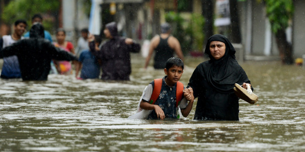 An Indian woman wades with her son through flooded street during heavy rain showers in Mumbai on August 29, 2017.Heavy rain brought India's financial capital Mumbai to a virtual standstill on August 29, flooding streets, causing transport chaos and prompting warnings to stay indoors. Dozens of flights and local train services were cancelled as rains lashed the coastal city of nearly 20 million people. / AFP PHOTO / PUNIT PARANJPE        (Photo credit should read PUNIT PARANJPE/AFP/Getty Images)