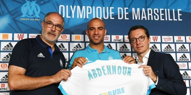 Olympique de Marseille's newly recruited player, Tunisien defender Aymen Abdennour (C), holds his new jersey next to Olympique de Marseille French president Jacques-Henri Eyraud (R) and Olympique de Marseille's sportive manager Andoni Zubizarreta during his official presentation, on August 30, 2017 at the Robert-Louis Dreyfus training centre in Marseille, southern France. Tunisian international defender Aymen Abdennour has joined Marseille on loan from Valencia, the French club announced on Augu