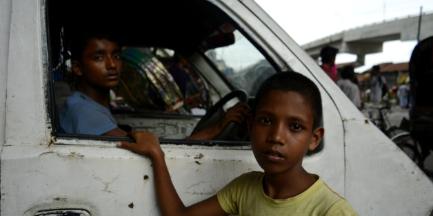 From left, Christy (14), Rony (10) look at the camera during a traffic signal on Thursday , July, 20 2017 in Dhaka, Bangladesh. Christy has been working as a driver for a year and Rony working around two weeks as a helperand want to be a driver soon, Rony said. According to the labour law in Bangladesh the minimum age for employment is 14 years. The enforcement of such labour law is virtually impossible in Bangladesh because most of child labourer are employed in the internal sector such as smal
