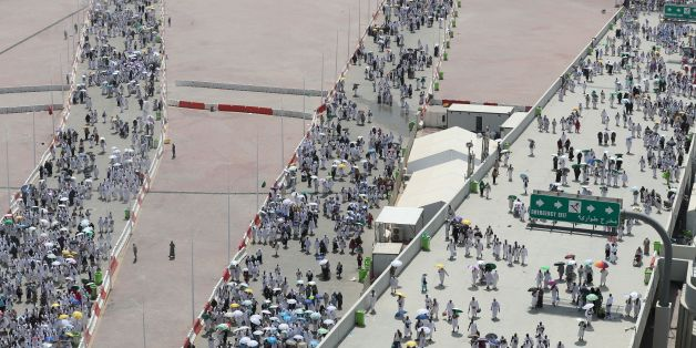 Muslim pilgrims, some holding umbrellas to protect themselves from the sun, head to take part in the symbolic stoning of the devil at the Jamarat Bridge in Mina, near Mecca, which marks the final major rite of the hajj on September 1, 2017.  / AFP PHOTO / KARIM SAHIB        (Photo credit should read KARIM SAHIB/AFP/Getty Images)