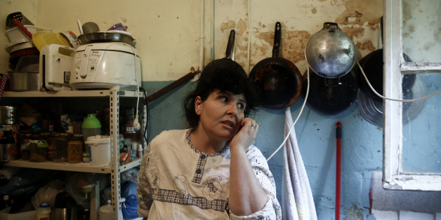"""Emine Kilic, a Turkish squatter and mother of 10, speaks on the phone inside a kitchen at the """"Prosfygika"""" housing complex in Athens November 24, 2013. It has been shelled, threatened with demolition and became such an eyesore that it was covered by a massive sheet during the 2004 Athens Olympics, but the historic 1930s housing complex built for Greeks fleeing Turkey is a hive of activity again. As Greece's six-year economic slump has increased the number of homeless to 20,000 in Athens alone, NGOs estimate, the """"Prosfygika"""" complex has become a haven for squatters and drug addicts as well as immigrants from Iran and elsewhere trying to cross into northern Europe through Greece's porous borders. Picture taken November 24, 2013.  REUTERS/Yorgos Karahalis (GREECE - Tags: SOCIETY IMMIGRATION POVERTY)"""