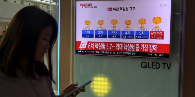 A woman walks past a television display at a train station in Seoul on September 3, 2017 showing a news broadcast with a graphic about a history of North Korean nuclear tests after news Pyongyang might have conducted a sixth test.North Korea appeared to carry out a sixth nuclear test on September 3, with seismic monitors measuring an 'explosion' of 6.3 magnitude near its main test site, sending tensions over its weapons ambitions to new heights. / AFP PHOTO / Ed JONES        (Photo credit should