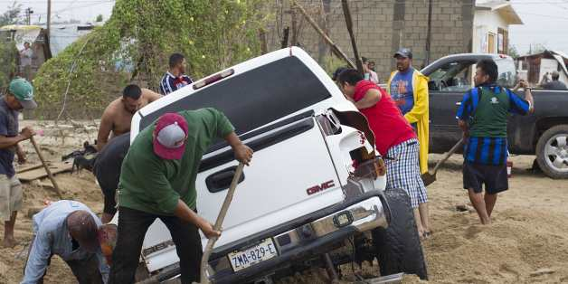Men attemp to rescue a truck trapped following heavy rains caused by tropical storm Lidia in Los Cabos, Baja California, Mexico on September 1, 2017.