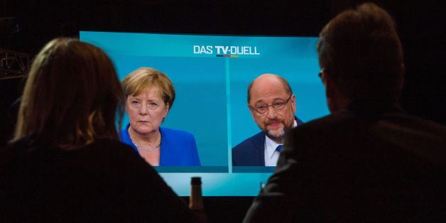 Journalists watch a televised debate between German Chancellor and leader of the conservative Christian Democratic Union (CDU) party Angela Merkel and Martin Schulz, leader of Germany's social democratic SPD party and candidate for Chancellor at a television studio in Berlin on September 3, 2017.