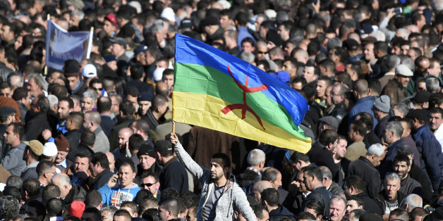 A man waves the Amazigh flag as thousands of mourners attend the funeral procession and burial of Hocine Ait-Ahmed, one of the fathers of Algeria's struggle for independence and a key opposition figure, in the Algerian village of Ait Ahmed on January 1, 2016. Ait-Ahmed's remains arrived in Algiers from Switzerland, where he died at the age of 89, for a state funeral the previous day before being transferred to his home village for his burial. The Amazighs, or Berbers, are the ethnicity indigenou