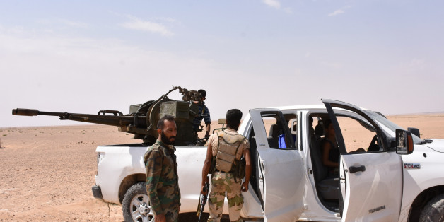 Syrian pro-government forces stand near an armed vehicle in Bir Qabaqib, more than 40 kilometres west of Deir Ezzor, after taking control of the area on their way to Kobajjep in the ongoing battle against Islamic State (IS) group jihadists on September 4, 2017. Syria's army are fighting the Islamic State group on the edges of Deir Ezzor seeking to break the siege of a government enclave and oust the jihadists from a key stronghold. / AFP PHOTO / George OURFALIAN        (Photo credit should read