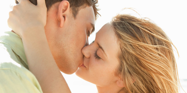 Romantic young couple kissing on a beach sunset.