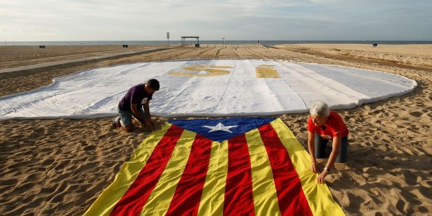 Two people unfold an 'Estelada' (Pro-independence Catalan flag) beside a banner reading 'SI' (Yes) on El Masnou beach, near Barcelona, on September 3, 2017, during an action called by ANC (Catalan National Assembly) to support a referendum on independence in Catalonia. / AFP PHOTO / Pau BARRENA CAPILLA        (Photo credit should read PAU BARRENA CAPILLA/AFP/Getty Images)
