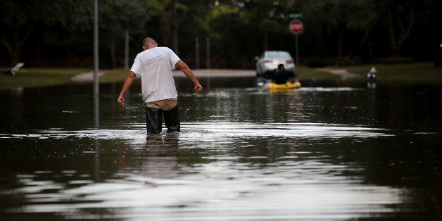 KATY, TX - SEPTEMBER 04:  A man walks through a flooded street on September 4, 2017 in Katy, Texas. Over a week after Hurricane Harvey hit Southern Texas, residents are beginning the long process of recovering from the storm.  (Photo by Justin Sullivan/Getty Images)