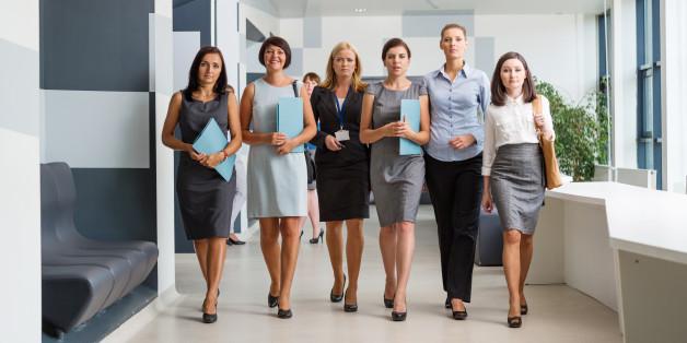 Group of confident businesswomen walking down the hall in modern interior.