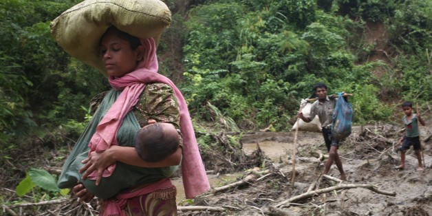 A rohingya woman carries her child in a sling while  walks through in hill after crossing the border into Bangladesh near cox's bazar area, teknaf. September 5, 2017  A total of 87,000 mostly Rohingya refugees have arrived in Bangladesh since violence erupted in neighbouring Myanmar on August 25, the United Nations said today, amid growing international criticism of Aung San Suu Kyi. Around 20,000 more were massed on the border waiting to enter, the UN said in a report. (Photo by Mushfiqul Alam/
