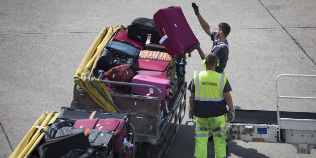 Airport staff unloads luggage from a plane at Tegel Airport on August 8, 2017 in Berlin.  / AFP PHOTO / AXEL SCHMIDT        (Photo credit should read AXEL SCHMIDT/AFP/Getty Images)
