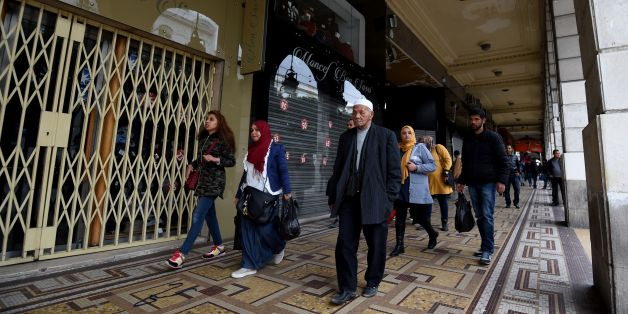 Tunisians walk past shops closed by their owners as part of a one-day strike in protest against the increase of the numbers of street vendors in the centre of Tunis on March 28, 2017. / AFP PHOTO / FETHI BELAID        (Photo credit should read FETHI BELAID/AFP/Getty Images)