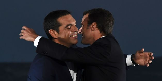French president Emmanuel Macron (R) embraces  Greek Prime Minister Alexis Tsipras   as he arrives to deliver a speech on the Pnyx hill with the Acropolis in the backround in Athens on September 7, 2017, as part of his two-day official visit to Greece.  Macron was holding talks on September 7 with Greek Prime Minister Alexis Tsipras and President Prokopis Pavlopoulos. / AFP PHOTO / ARIS MESSINIS        (Photo credit should read ARIS MESSINIS/AFP/Getty Images)
