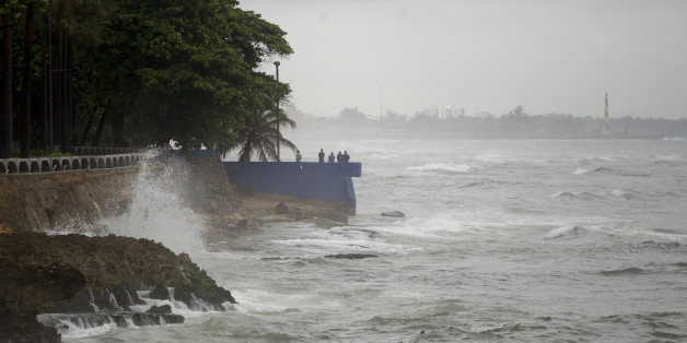 People stand by the sea in the rain in the La Cienaga neighborhood on September 7, 2017, as Hurricane Irma approaches. 
