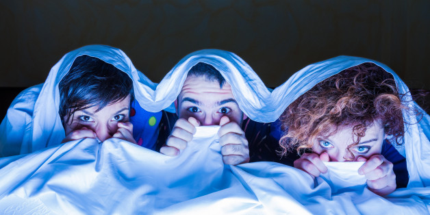 Young people watching a movie on tv under the sheets.
