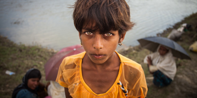 A Rohingya ethnic minority girl from Myanmar poses as they alight from a local boat on which they crossed a river, after crossing over to the Bangladesh side of the border near Cox's Bazar's Whykkyong Lamba Bill area, Thursday, Sept. 7, 2017. Tens of thousands more people have crossed by boat and on foot into Bangladesh in the last two weeks as they flee violence in western Myanmar. (Photo by Ahmed Salahuddin/NurPhoto via Getty Images)