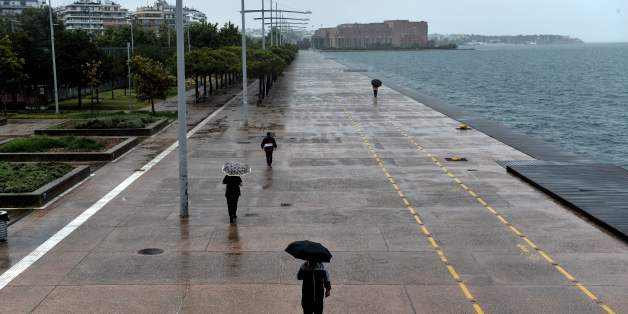 People walk with umbrellas under a rainfall on the waterfront of Thessaloniki on July 17, 2017.  Greeks are bearing the brunt of a weather phenomenon called Medusa with heavy rains, hailstorms, and strong winds. / AFP PHOTO / SAKIS MITROLIDIS        (Photo credit should read SAKIS MITROLIDIS/AFP/Getty Images)