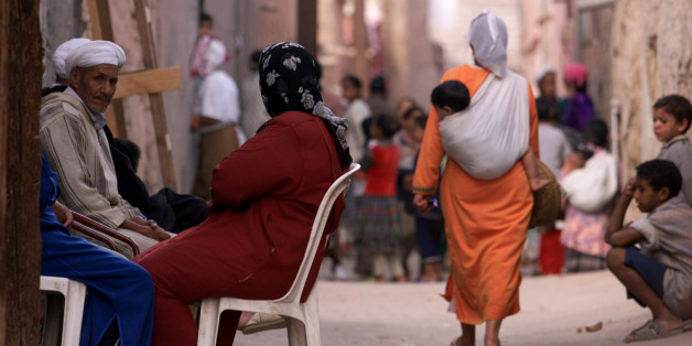 A Moroccan woman carries a young child in a sling on her back as she walks along one of the many narrow streets in Marrakech, November 6, 2001. REUTERS/Zohra Bensemra  JES/