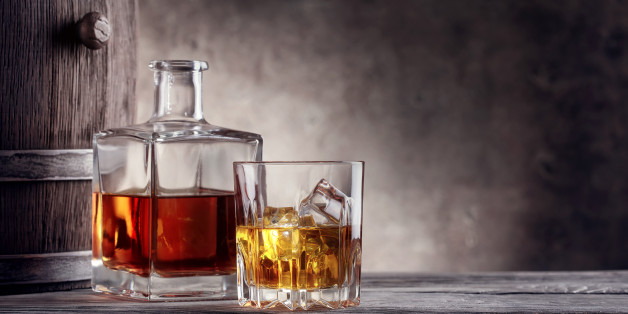 Square decanter and a glass of whiskey with ice on background barrel
