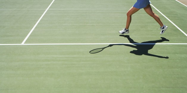Shadow and legs of person playing tennis
