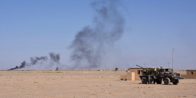Syrian pro-government forces hold a position near the village of al-Maleha, in the northern countryside of Deir Ezzor, on September 9, 2017, during the ongoing battle against Islamic State (IS) group jihadists.Syrian troops broke the Islamic State group's siege of the eastern Deir Ezzor military airport, dealing a new blow to the jihadists who were facing a new offensive from US-backed fighters elsewhere in the province. / AFP PHOTO        (Photo credit should read /AFP/Getty Images)