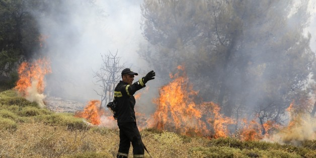 ATHENS, GREECE - AUGUST 15: Firefighters  battle with a wildfire which has been continuing for two days, in Kalamos region of Athens, Greece on August 15, 2017. High winds are driving wildfires near the Greek capital Athens, forcing residents and holidaymakers to flee. More than 20 houses have already been damaged as the blazes, which began on Sunday, burned through pine forests north of the city. Around 150 firefighters, with the help of helicopters and planes, are still battling to contain fires in the coastal areas of Kalamos and Varnava. (Photo by Ayhan Mehmet/Anadolu Agency/Getty Images)