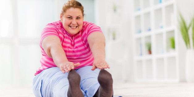 Young overweight smiling woman sitting on the floor and stretching while looking at camera.
