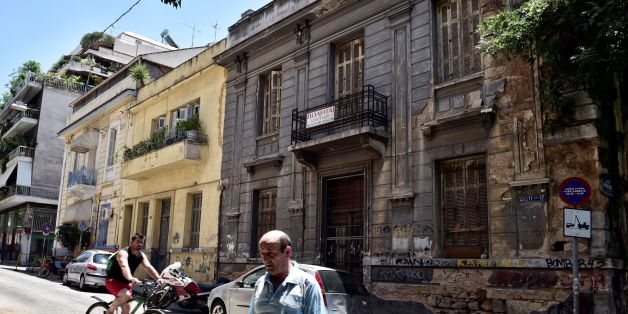 People pass a neoclassical  building for sale in one of the oldest districts of Athens on July 7, 2017.