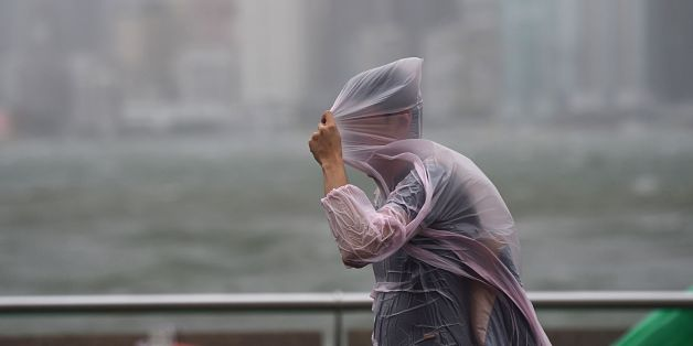 A man shields himself with his plastic poncho during heavy winds and rain brought on by Typhoon Hato in Hong Kong on August 23, 2017. Typhoon Hato smashed into Hong Kong on August 23 with hurricane force winds and heavy rains in the worst storm the city has seen for five years, shutting down the stock market and forcing the cancellation of hundreds of flights. / AFP PHOTO / Anthony WALLACE        (Photo credit should read ANTHONY WALLACE/AFP/Getty Images)