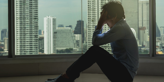 depressed man sitting head in hands on the interior Skyscraper with low light environment beside the windows over the cityscape background, dramatic concept