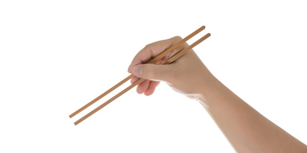 hand holding chopsticks, isolated on white background with clipping path
