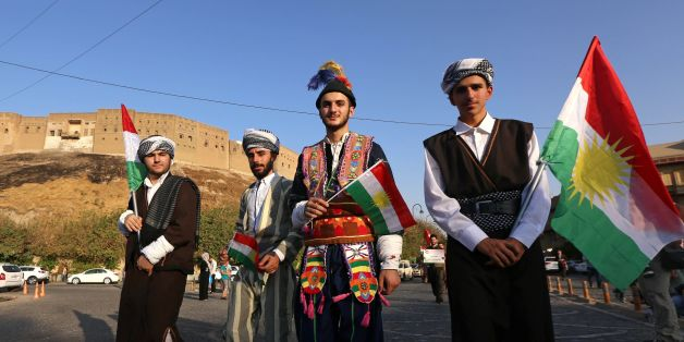 Iraqis dressed in traditional clothing and holding Kurdish flags walk near the citadel in Arbil, the capital of the autonomous Kurdish region of northern Iraq, as they head to a gathering to urge people to vote in the upcoming independence referendum on September 13, 2017. Iraq's autonomous Kurdish region will hold a historic referendum on statehood in September 2017, despite opposition to independence from Baghdad and possibly beyond. / AFP PHOTO / SAFIN HAMED        (Photo credit should read S