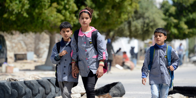 Tunisian school children walk past on April 14, 2016 a road block set up by residents of the island of Kerkennah during a series of social protests related to Tunisia's natural gas facility of UK based oil company Petrofac. Petrofac facility on Kerkennah has halted production since social protests started in January 2016.  / AFP / FETHI BELAID        (Photo credit should read FETHI BELAID/AFP/Getty Images)