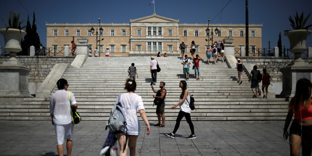 People make their way on main Syntagma square as the parliament building is seen in the background in Athens, Greece, July 24, 2017. REUTERS/Alkis Konstantinidis