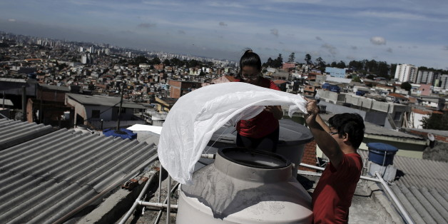 People hold a mosquito net before placing it over a water container on the roof of their house in Brasilandia slum, in Sao Paulo, Brazil, February 11, 2015. Picture taken on February 11, 2015. REUTERS/Nacho Doce