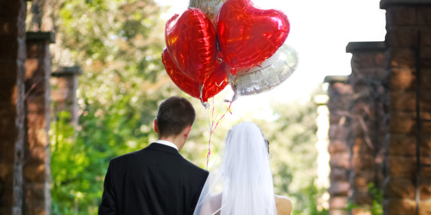 Bridal couple walking a lonely path with heart shaped balloons.