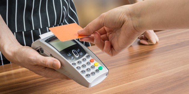 Customer is paying with contactless credit card in shop.