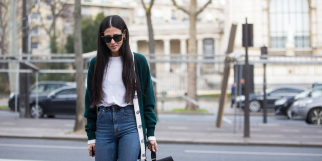 Designer Gilda Ambrosio wears black sunglasses, green cardigan, white top, high-waisted jeans, and and a black Chanel bag at the Ellery show at Palais de Tokyo on March 07, 2016 in Paris, France.