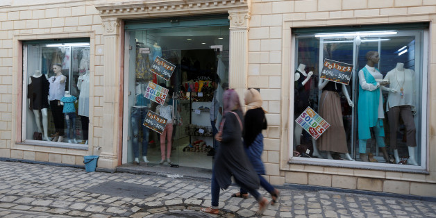 Women look at sale signs placed on a shop's windows while walking through central Mehdia,Tunisia, August 17, 2017. REUTERS/Zoubeir Souissi