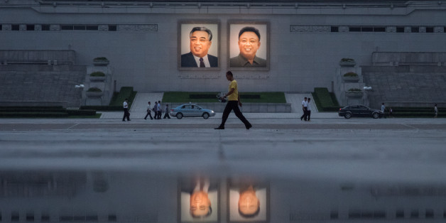 TOPSHOT - In a photo taken on July 21, 2017 pedestrians and vehicles pass before the portraits of late North Korean leaders Kim Il-Sung (L) and Kim Jong-Il (R) in Pyongyang. China urged North Korea August 6 to make a 'smart decision', after the United Nations imposed tough new sanctions on the isolated regime over its missile and nuclear programmes. / AFP PHOTO / Ed JONES        (Photo credit should read ED JONES/AFP/Getty Images)