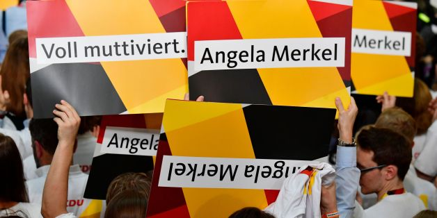 Supporters of the Christian Democratic Union (CDU) react with banners as exit poll results were broadcasted on public television at an election night event at the party's headquarters in Berlin during the general election on September 24, 2017.Germany voted in a general election expected to hand Chancellor Angela Merkel a fourth term, while the hard-right Alternative for Germany (AfD) party is predicted to win its first seats in the national parliament. / AFP PHOTO / Tobias SCHWARZ        (Photo