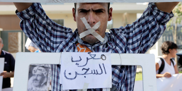 "A relative of the leaders of Morocco's Hirak protest movement displays a placard that reads ""Moroccan jail"" during the trial outside the court in Casablanca, Morocco September 12, 2017. REUTERS/Youssef Boudlal"