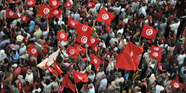 Tunisian demonstrators wave their national flag and shout slogans during a protest against the country's Islamist-led government in front of the Constituent Assembly headquarters in Tunis on August 13, 2013, which marks national women's day, as the president proposed a national unity cabinet to end a protracted crisis. The government, led by the Islamist Ennahda party, and its detractors have been locked in a bitter feud sparked by the July assassination of an opposition politician, the second such killing this year. AFP PHOTO / FETHI BELAID        (Photo credit should read FETHI BELAID/AFP/Getty Images)