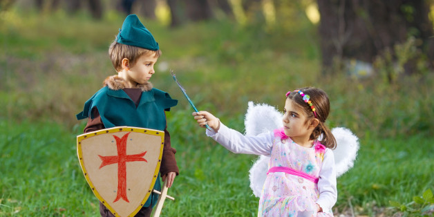 Cute little children dressed up as a fairy and a knight playing in a forest